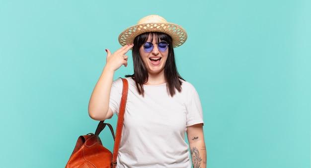 Mulher jovem viajante parecendo infeliz e estressada, gesto de suicídio fazendo sinal de arma com a mão, apontando para a cabeça