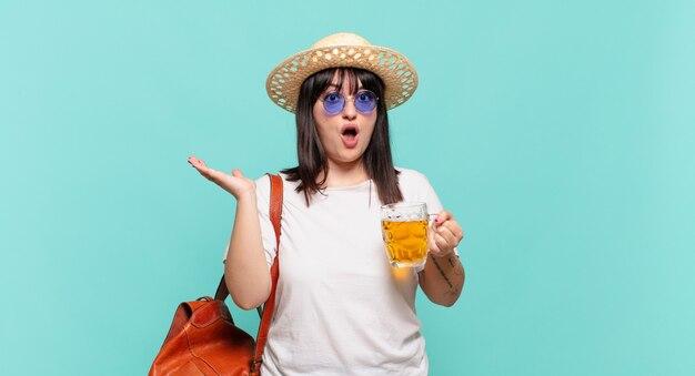 Mulher jovem viajante parecendo surpresa e chocada, com o queixo caído segurando um objeto com a mão aberta na lateral