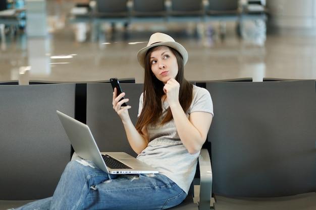 Mulher jovem viajante pensativa, turista, com chapéu e laptop pensando, segurar o telefone celular, esperando no saguão do aeroporto internacional
