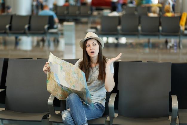 Mulher jovem viajante preocupada segurando um mapa de papel, procurando a rota, espalhando as mãos, esperando no saguão do aeroporto