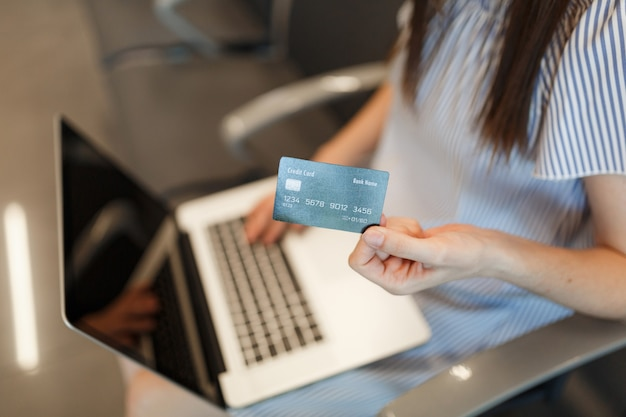 Mulher jovem viajante recortada trabalhando em um laptop com tela em branco, segurando o cartão de crédito enquanto espera no saguão do aeroporto