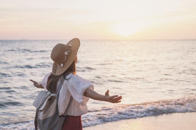 Mulher jovem viajante relaxante na praia tropical ao pôr do sol