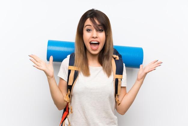 Mulher jovem viajante sobre fundo branco com expressão facial chocada