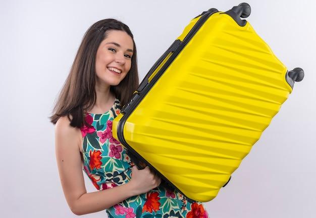 Mulher jovem viajante sorridente segurando mala na parede branca isolada