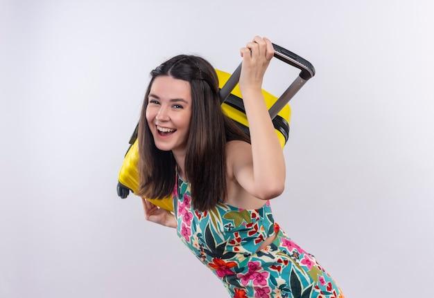 Mulher jovem viajante sorridente, usando um vestido multicolorido, segurando um celular nas costas do ombro na parede branca