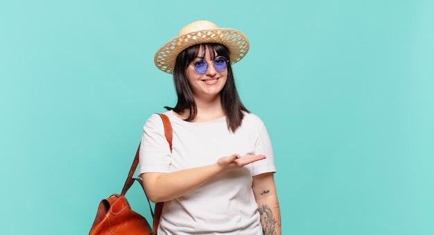 Mulher jovem viajante sorrindo alegremente se sentindo feliz e mostrando algo no espaço da cópia com a palma da mão