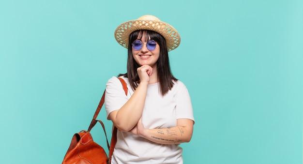 Mulher jovem viajante sorrindo com uma expressão feliz e confiante com a mão no queixo, pensando e olhando para o lado