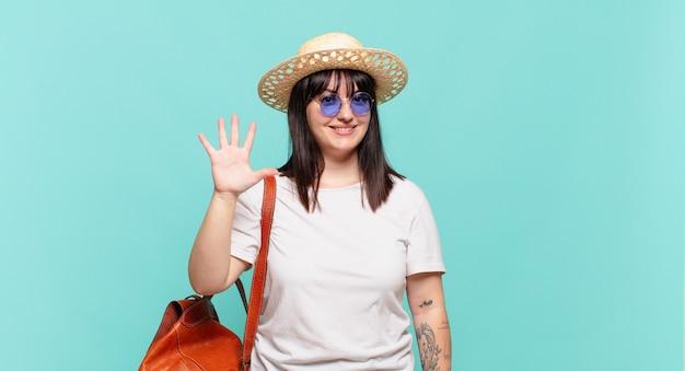 Mulher jovem viajante sorrindo e parecendo amigável, mostrando o número cinco ou quinto com a mão em contagem regressiva
