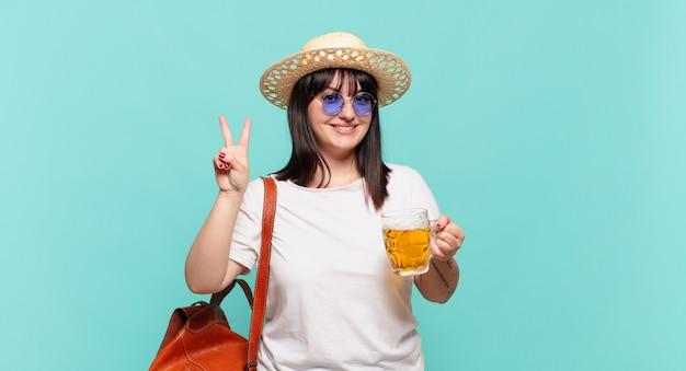 Mulher jovem viajante sorrindo e parecendo amigável, mostrando o número dois ou o segundo com a mão para a frente, em contagem regressiva