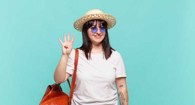 Mulher jovem viajante sorrindo e parecendo amigável, mostrando o número quatro ou o quarto com a mão em contagem regressiva