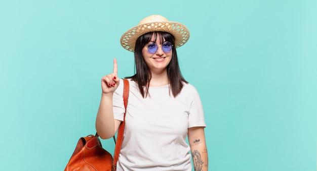 Mulher jovem viajante sorrindo e parecendo amigável, mostrando o número um ou primeiro com a mão em contagem regressiva