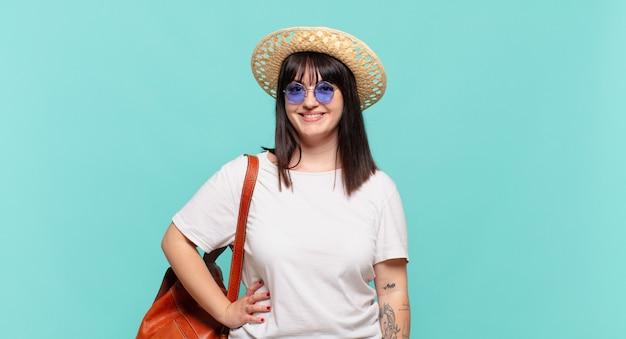 Mulher jovem viajante sorrindo feliz com uma mão no quadril e atitude confiante, positiva, orgulhosa e amigável