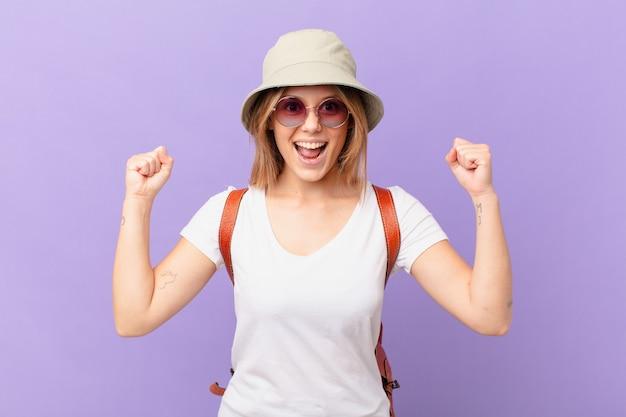 Mulher jovem viajante turista chocada, rindo e comemorando o sucesso