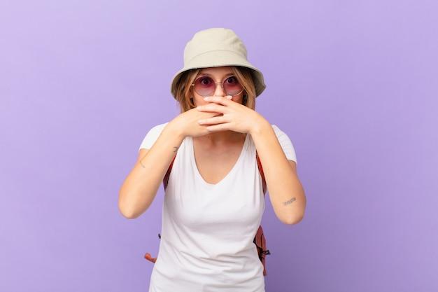 Mulher jovem viajante turista cobrindo a boca com as mãos com um choque