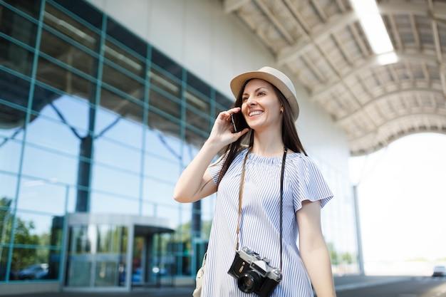 Mulher jovem viajante turista com câmera fotográfica vintage retrô falando no celular, ligando para um amigo,