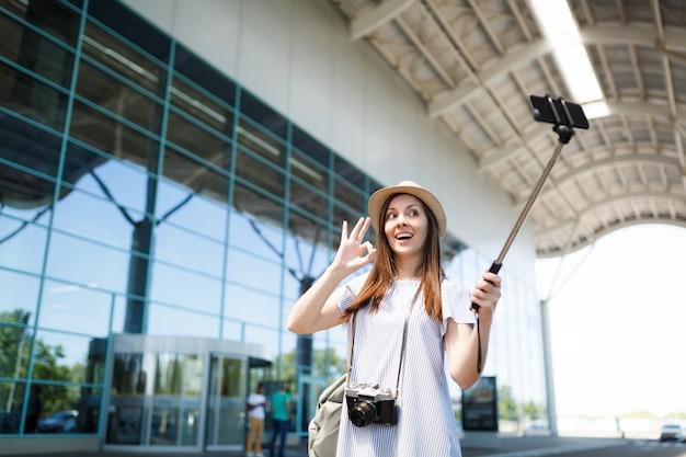 Mulher jovem viajante turista com câmera fotográfica vintage retrô mostra sinal de ok fazendo selfie no celular com monopé de vara egoísta no aeroporto