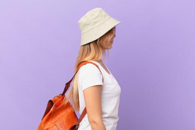 Mulher jovem viajante turista em vista de perfil pensando, imaginando ou sonhando acordada
