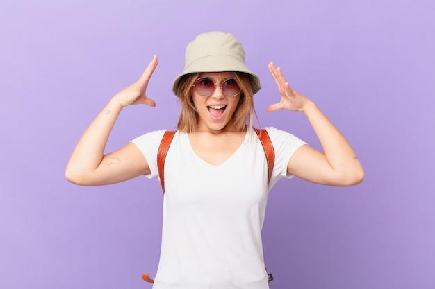 Mulher jovem viajante turista gritando com as mãos para cima