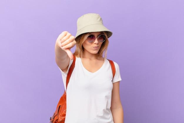 Mulher jovem viajante turista mostrando os polegares para baixo