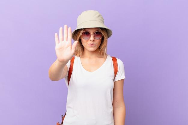 Mulher jovem viajante turista olhando séria, mostrando a palma da mão aberta fazendo gesto de pare
