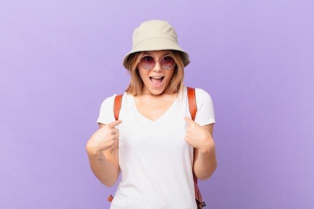 Mulher jovem viajante turista se sentindo feliz e apontando para si mesma com um olhar animado