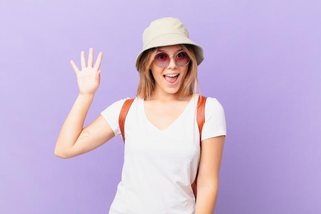 Mulher jovem viajante turista sorrindo alegremente acenando com a mão dando as boas-vindas e cumprimentando