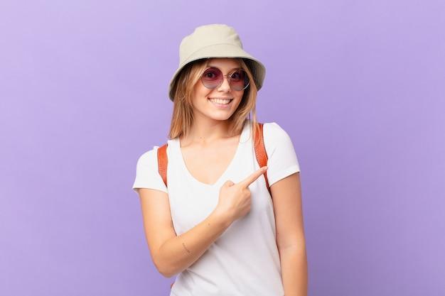 Mulher jovem viajante turista sorrindo alegremente se sentindo feliz e apontando para o lado