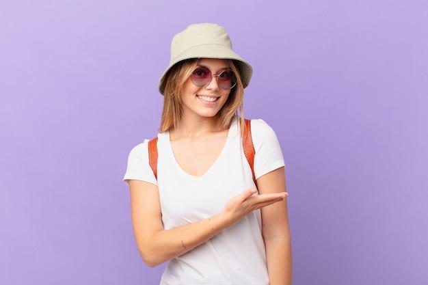Mulher jovem viajante turista sorrindo alegremente se sentindo feliz e mostrando um conceito
