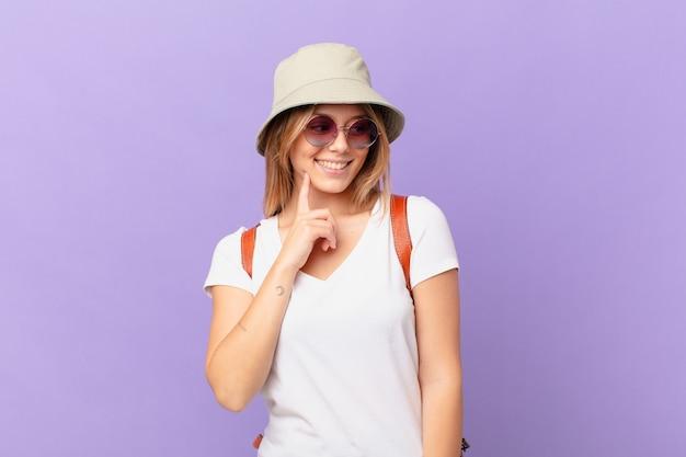 Mulher jovem viajante turista sorrindo com uma expressão feliz e confiante com a mão no queixo