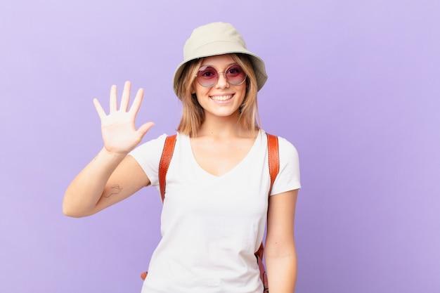 Mulher jovem viajante turista sorrindo e parecendo amigável mostrando o número cinco