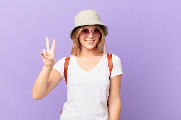 Mulher jovem viajante turista sorrindo e parecendo amigável mostrando o número dois