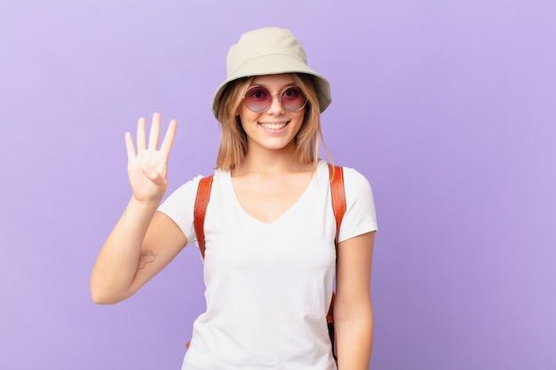 Mulher jovem viajante turista sorrindo e parecendo amigável, mostrando o número quatro