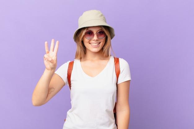 Mulher jovem viajante turista sorrindo e parecendo amigável mostrando o número três