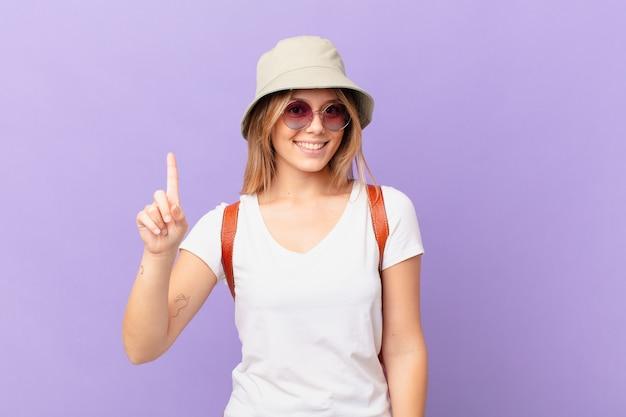 Mulher jovem viajante turista sorrindo e parecendo amigável mostrando o número um