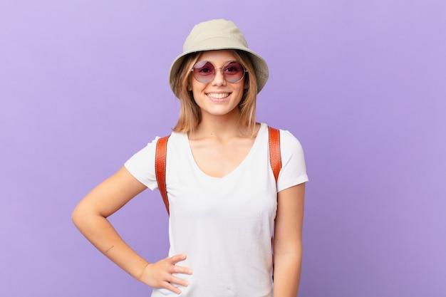 Mulher jovem viajante turista sorrindo feliz com uma mão no quadril e confiante