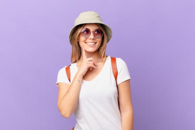 Mulher jovem viajante turista sorrindo feliz e sonhando acordada ou duvidando