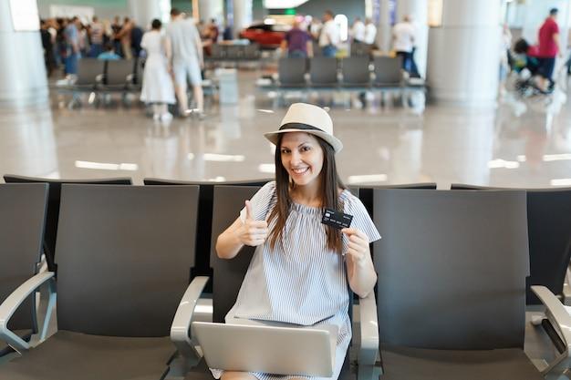 Mulher jovem viajante turista trabalhando em um laptop, segurando o cartão de crédito, aparecendo o polegar, esperando no saguão do aeroporto internacional