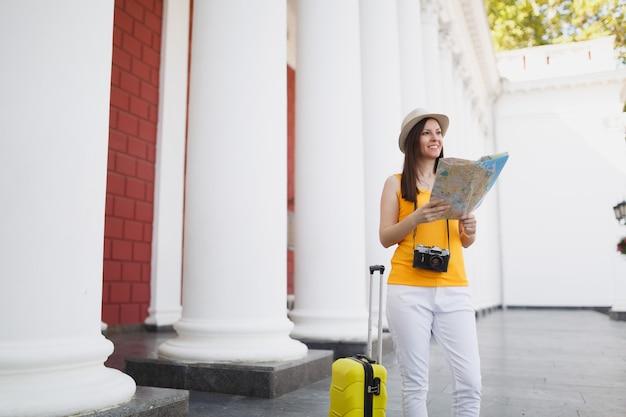 Mulher jovem viajante turística em roupas amarelas com câmera de foto vintage retrô mala segurando o mapa da cidade ao ar livre da cidade. garota viajando para o exterior para viajar no fim de semana. estilo de vida da viagem de turismo.