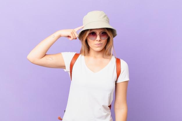 Mulher jovem viajante turística se sentindo confusa e perplexa por mostrar que você é louco