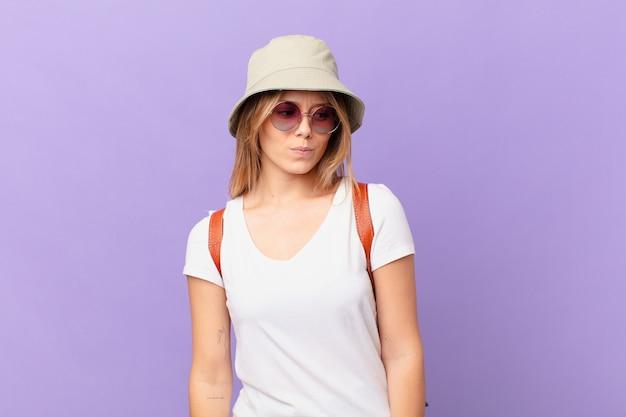 Mulher jovem viajante turística se sentindo triste, chateada ou com raiva e olhando para o lado
