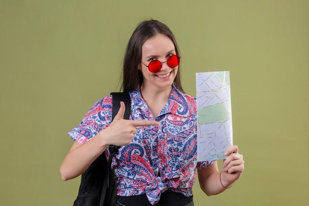Mulher jovem viajante usando óculos escuros vermelhos e com uma mochila segurando um mapa apontando com o dedo indicador para ele, sorrindo alegremente em pé sobre um fundo azul