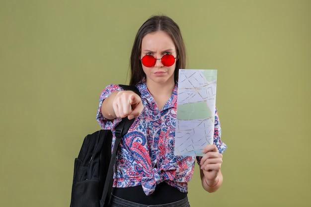 Mulher jovem viajante usando óculos escuros vermelhos e com uma mochila segurando um mapa descontente apontando para a câmera com o dedo com expressão de raiva em pé sobre o fundo verde