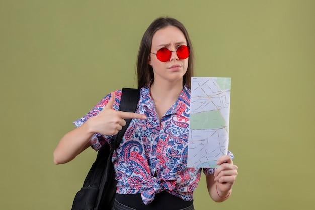 Mulher jovem viajante usando óculos escuros vermelhos e com uma mochila segurando um mapa descontente, apontando para ele com o dedo indicador em pé sobre o fundo verde