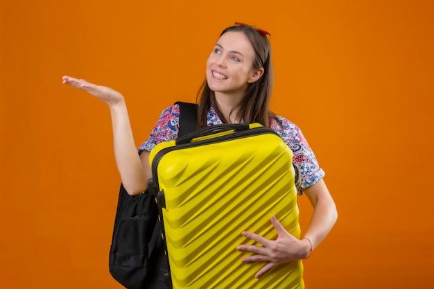 Mulher jovem viajante usando óculos escuros vermelhos na cabeça em pé com a mochila segurando a mala, olhando para o lado e apresentando com o braço da mão algo sorrindo com uma cara feliz sobre o background laranja