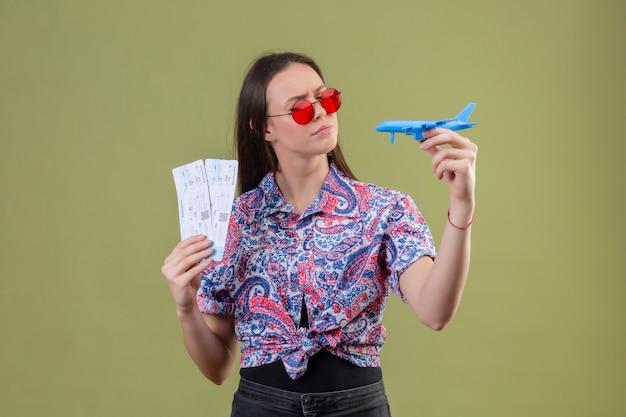 Mulher jovem viajante usando óculos escuros vermelhos segurando bilhetes e avião de brinquedo, olhando-o com expressão pensativa com o rosto carrancudo sobre parede verde