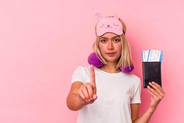 Mulher jovem viajante venezuelano segurando um passaporte isolado no fundo rosa, mostrando o número um com o dedo.