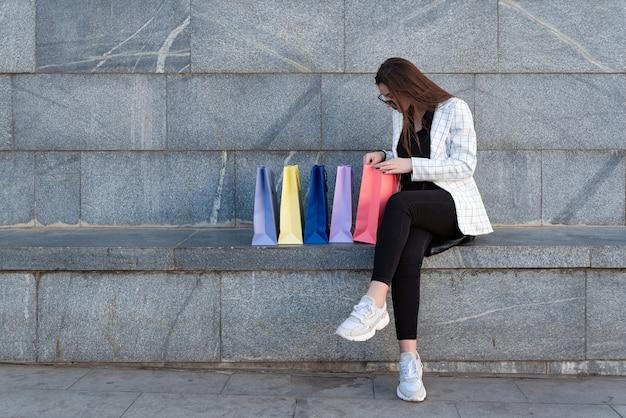 Mulher jovem viciada em compras com muitos sacos de compras ao ar livre. compra bem-sucedida.