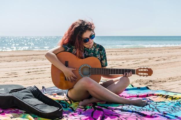Mulher jovem, violão jogo, praia