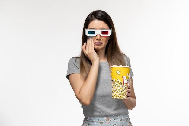 Mulher jovem, vista frontal, comendo pipoca e assistindo filme com óculos de sol d na superfície branca clara