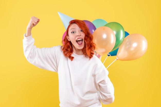 Mulher jovem, vista frontal, escondendo balões coloridos atrás das costas em um fundo amarelo.